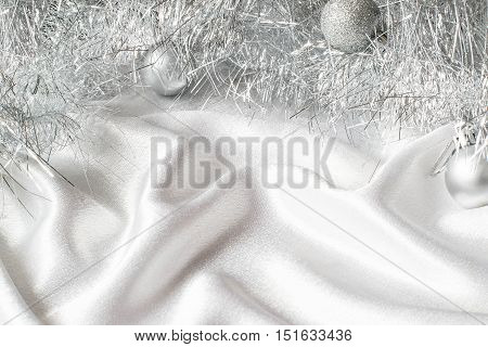 Festive Christmas background with Christmas-tree tinsel glistening balls on white satin fabric. Free space for text
