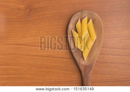 Penne into a spoon over a wooden table