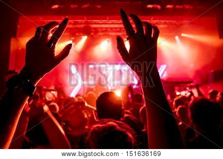 Close up of hands of a young woman at concert, small depth of view, focus at the hands