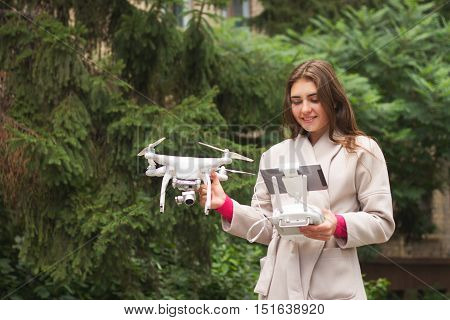 Young Woman Is Standing And Holding Drone.
