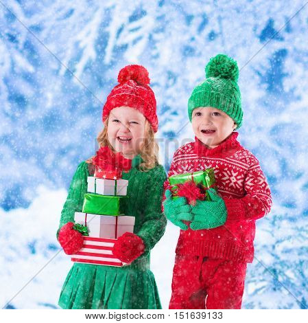 Little girl and boy in red and green knitted hat holding Christmas present boxes in winter park on Xmas eve. Kids play outdoor in snowy winter forest. Children opening presents. Toddler kid with gifts