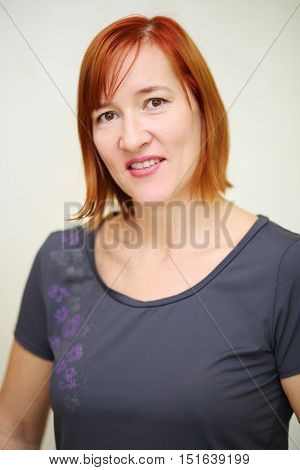 Portrait of happy middle aged woman with red hair in grey t-shirt