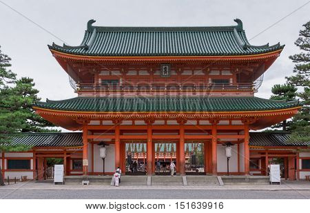 Kyoto Japan - September 15 2016: Monumental vermilion entrance gate of the Heian Shinto Shrine. Green roof in Japanese style. Gray skies. People walk up the steps.