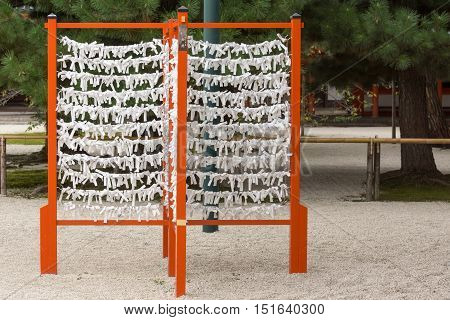 Kyoto Japan - September 15 2016: Vermilion rack with white paper prayer strips at Heian Shrine. People print or write their pleas and wishes on paper and leave it at the shrine.