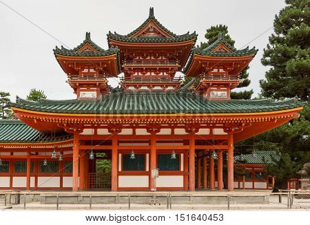 Kyoto Japan - September 15 2016: Vermilion structure with green roofs consists of ground level with three elaborate towers on top. Frontal view with gray skies and green trees.