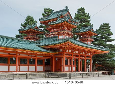 Kyoto Japan - September 15 2016: Vermilion structure with green roofs consists of ground level with four elaborate towers on top in view. Gray skies and green trees.
