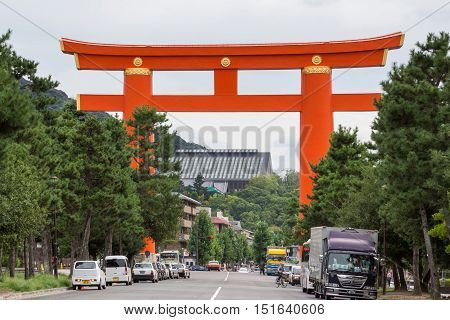 Kyoto Japan - September 15 2016: Giant vermillion Torii on the street leading to Heian Shrine. People and cars show the height and width of the gate.