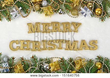 Merry Christmas Golden Text And Spruce Branch And Christmas Decorations On A White