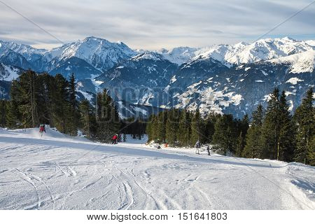 Group of skiers skiing down the mountain ski slopes at sunny day