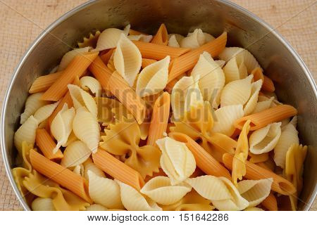 Stainless Mixing bowl of mixed variety farfalle, penne and seashell shaped vegetable and wheat pasta