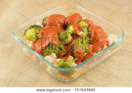Casserole preparation with pasta, canned chicken chunks and steamed broccoli and marinara sauce