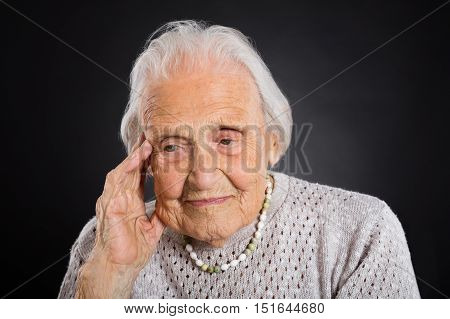 Portrait Of Thoughtful Senior Woman Over Grey Background
