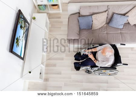High Angle View Of Elder Woman Watching Movie On Television At Home