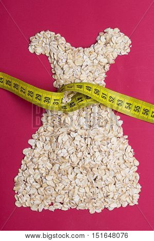 Dieting healthy eating slim down concept. Female dress shape made from oatmeal with measuring tape around thin waist on red