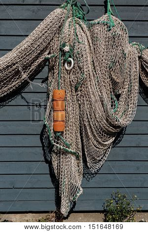 Newfoundland fish net and buous hanging on a rustic wall.