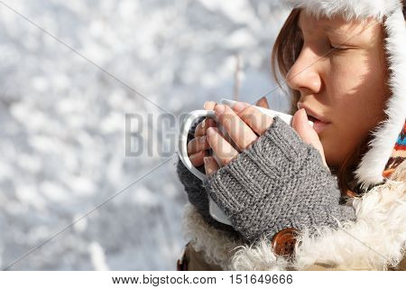 Beautiful young woman in gray fingerless knitted mittens cap with ear flaps and coat with white fur drinking tea or coffee holding white cup in hands at the background of snowy forest.