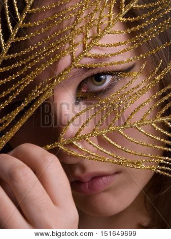 Young beautiful woman with black and gold eyeliner make-up looking golden feather. Close up.