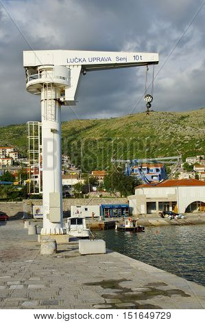 Senj Croatia - September 16 2016: a small town in northern Croatia located on the Adriatic coast. Small port crane on the jetty. Some people are visiable on the quay.