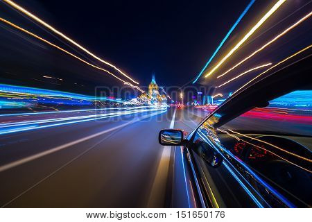 The car moves at great speed at the night. Blured road with lights and car on high speed.