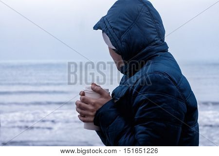 man warms his hands with cup of takeaway coffee. Sea is on background.