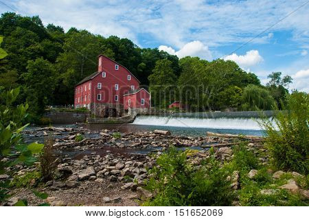 A red mill surrounded by greenery, beside the Raritan River in Clinton, New Jersey on a summer afternoon.