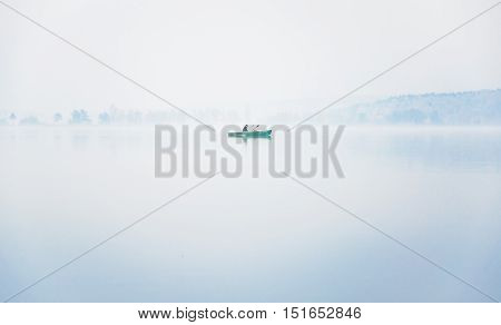 Alone fisherman on the boat in a thick fog on the lake on an autumn morning in calm weather