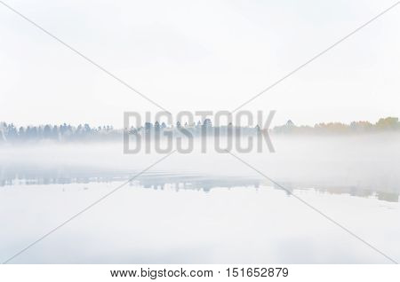 Very thick fog on the lake Senezh in Solnechnogorsk fall in calm weather. Autumn morning water landscape