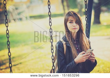 Gorgeous young blonde millennial Caucasian woman in park on a swing using smart phone. Cool teenage girl outdoors using mobile phone. Matte filter applied.