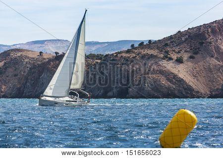 Sailing yacht in the finish during the race regattas near the coastal cliffs in the Aegean sea.