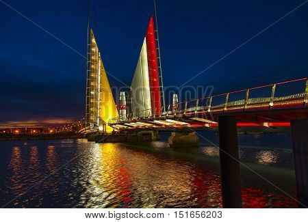 The Twin Sails Lifting Bridge was illuminated gold in support of childhood cancer. The red gold and white lights are reflected in the waters of Holes Bay in Poole Harbour