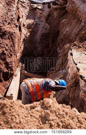 construction worker digging trench to repair broken roadway