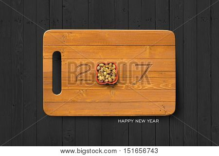 2017 Happy New Year Concept 2017 Text on Wooden Antiseptic Cutting Board With Pistachio Bowl on Grey Wall Texture. Selection Path Included.
