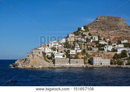 Coast with buildings and the entrance to the Marina on the Hydra island, Greece.