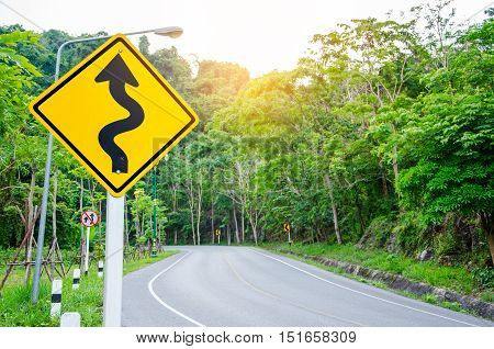 Curvy road sign to the mountain in rural area.