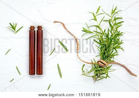 Fresh Branch Of Rosemary  With Bottle Essential Oil Setup On White Wooden Table. Nature Aromatherapy
