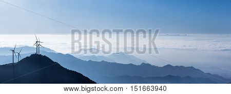wind turbines and the sea of clouds on stretches of blue mountains backgrounda panoramic view of the beautiful natural scenery