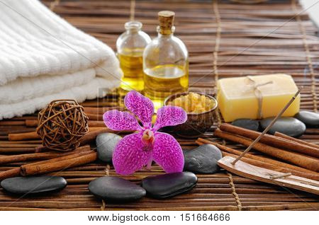 Spa setting with pink orchid ,towel, stones ,candle ,cinnamon with mat texture