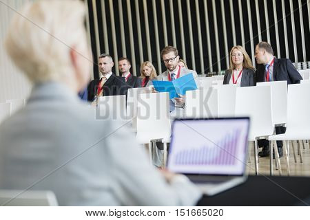 Business people sitting in seminar hall
