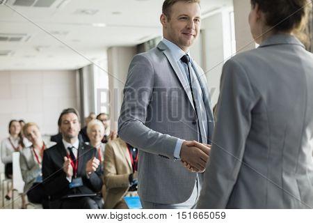 Confident businessman greeting public speaker during seminar