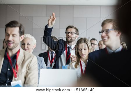 Businessman asking questions during seminar