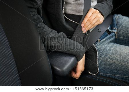 Closeup of woman fastening seat belt in car
