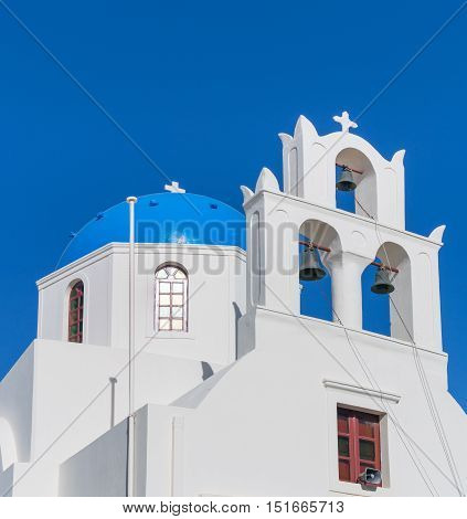 White church tower with three bells against blue sky background in Oia village Santorini island Greece