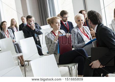 Businessman talking to businesswomen in seminar hall