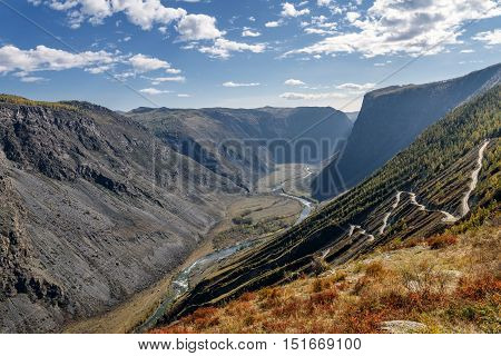 The picturesque top view on the steep winding gravel road through the pass going up the mountain the valley between the mountains and the river on a background of blue sky and clouds