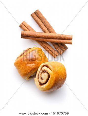 Mini cinnamon buns and cinnamon sticks isolated on white background. Top view.