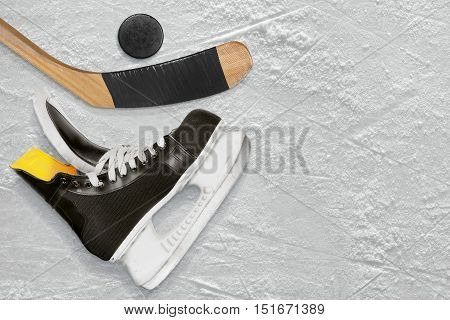 Hockey sticks skate and puck on the ice. Texture background