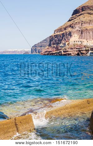 The waves beat against the rocks on a sunny summer day at Old port Ammoudi of Oia village at Santorini island in Aegean sea Greece