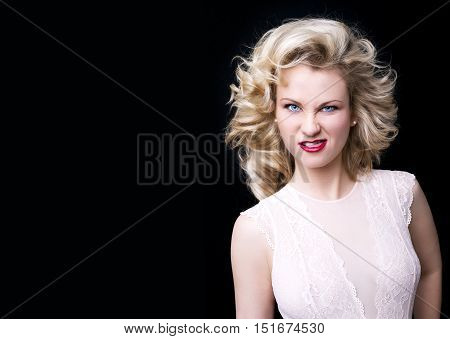 A portrait of young beautiful woman pulling a ridiculous face on black background