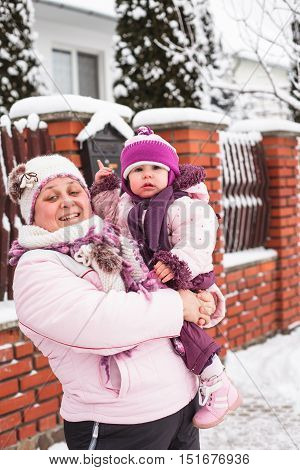 Winter portrait of grandmother with a granddaughter in the yard