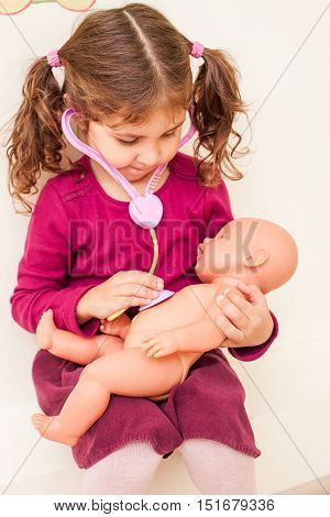 Girl with stethoscope is playing the doctor and listening the doll